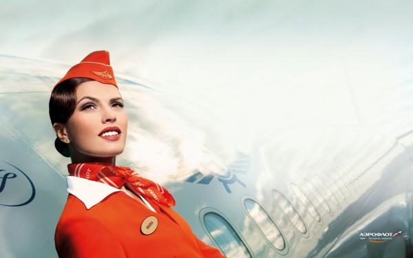 Фото стюардессы Аэрофлота в шляпке пилотке на фоне самолета