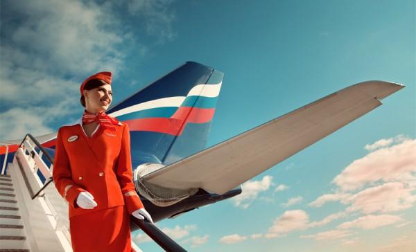 Фото стюардессы в шляпке-пилотке на фоне самолета